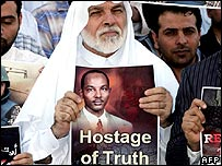 A protestor holds an image of Sami al-Haj
