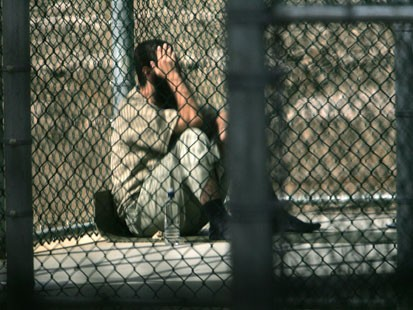 A detainee sits alone during his recreation period