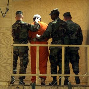 A Guantanamo detainee escorted by guards