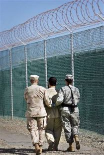A prisoner at Guantanamo is escorted by guards