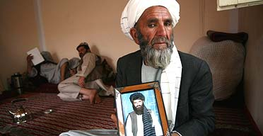 Abdullah Mujahid's father holds a photo of his son