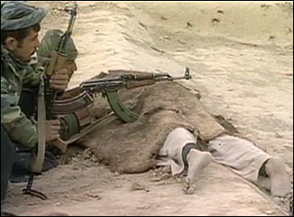 Alliance soldier rest guns on a corpse at Qala-i-Janghi