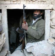An Afghan soldier sits in the entrance of one of the Tora Bora caves