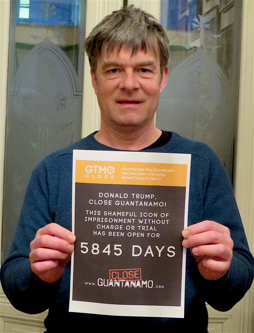 Andy Worthington launching the new Close Guantanamo initiative for 2018, showing how long the prison has been open - with the first poster showing 5,845 days on January 11, 2018, the 16th anniversary of its opening. Throughout the year, the Gitmo Clock website will count exactly how many days, hours, minutes an seconds Guantanamo has been open, and posters can be printed from the page for people to take photos with and send to the Close Guantanamo campaign.