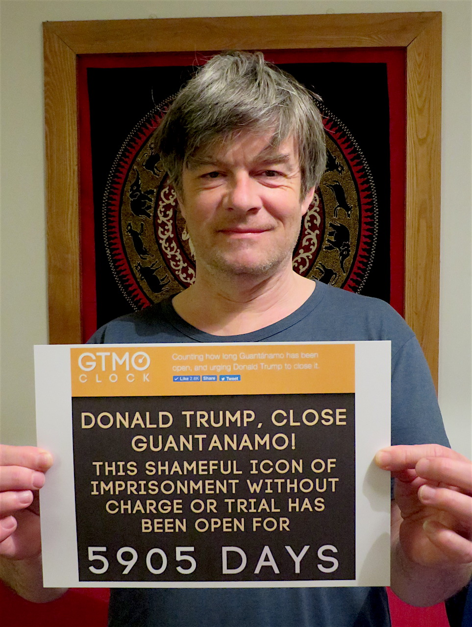 Andy Worthington calling on Donald Trump to close Guantanamo today, March 12, 2018. Andy is holding poster showing that, today, the prison has been open for 5,905 days.