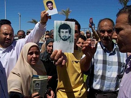 People holding up photos of their missing relatives at a protest to mark the 12th anniversary of the Abu Salim prison massacre, on June 17, 2008, in Benghazi