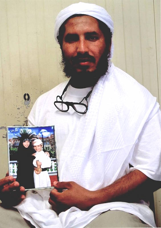 Guantanamo prisoner Ahmed al-Darbi, with a photo of his children, in a photo taken several years ago by representatives of the International Committee of the Red Cross.
