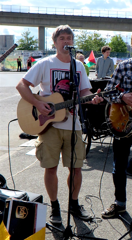 Andy Worthington, wearing a Guantanamo T-shirt designed by Shepard Fairey for Witness Against Torture, playing with The Four Fathers at the Festival of Resistance against the DSEI arms fair in London on September 9, 2017.