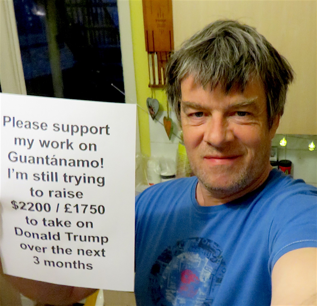 Andy Worthington holding up a poster advertising a fundraising appeal for his independent writing and campaigning on Guantanamo.