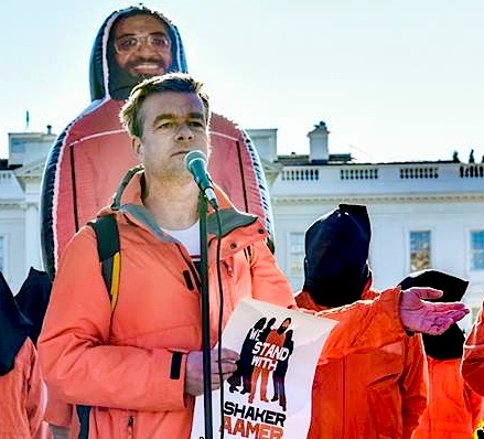 Andy Worthington speaking outside the White House on January 11, 2016, the 14th anniversary of the opening of Guantanamo. Behind him is the giant inflatable figure of Shaker Aamer that was at the heart of the We Stand With Shaker campaign (Photo: Justin Norman).