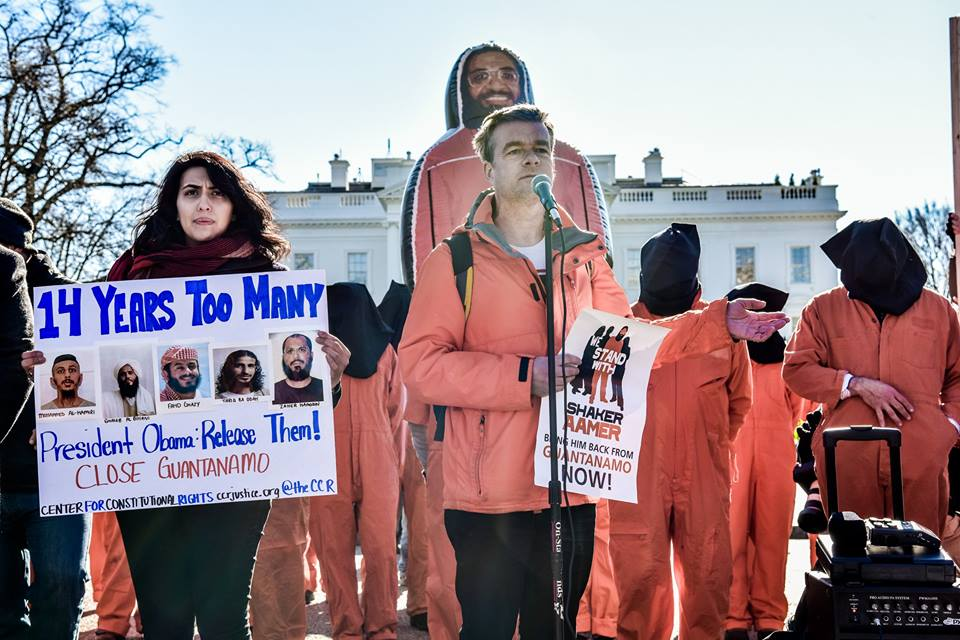 Andy Worthington (center) and Aliya Hussain of the Center for Constitutional Rights outside the White House on January 11, 2016, the 14th anniversary of the opening of the prison. Behind Andy is the giant inflatable figure of Shaker Aamer that was at the heart of the We Stand With Shaker campaign (Photo: Justin Norman for Witness Against Torture).