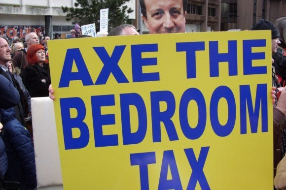 "A campaigner holding up an ""Axe the Bedroom Tax"" sign at a protest in 2013."