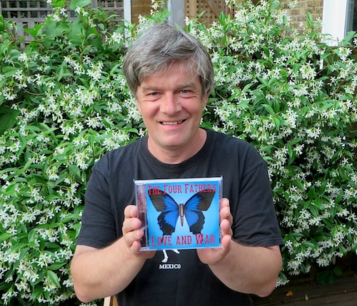 Andy Worthington holding up a copy of 'Love and War' by The Four Fathers, after collecting the first copies from the manufacturers on July 3, 2015.