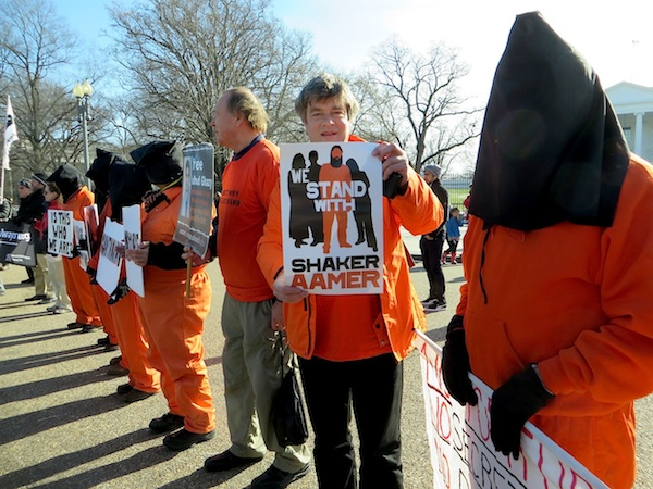 Andy Worthington standing with the poster for the We Stand With Shaker campaign at the protest against Guantanamo outside the White House on January 11, 2015, the 13th anniversary of the opening of the prison (Photo: Medea Benjamin for Andy Worthington).