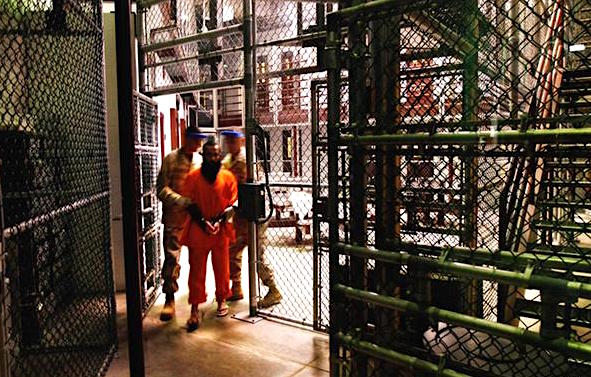 A prisoner being moved by guards in Camp Six at Guantanamo (Photo: J. Moore, Getty Images).