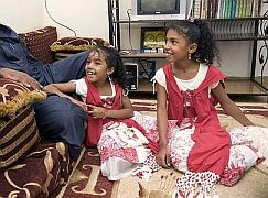 """Salim Ahmed Hamdan sits with daughters, Selma, left, and Fatima, at their home in Yemen. He invited the Star inside on condition he not be photographed"" (Photo by Lucas Oleniuk for the Toronto Star)"