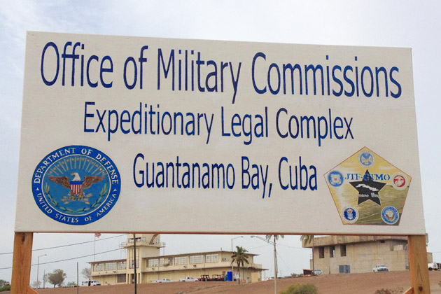 A sign for the military commissions at Guantanamo. Behind is the first courtroom used for the commissions, which is no longer in use, but photos of the current courtroom are not allowed. (Photo: Cora Currier/ProPublica).