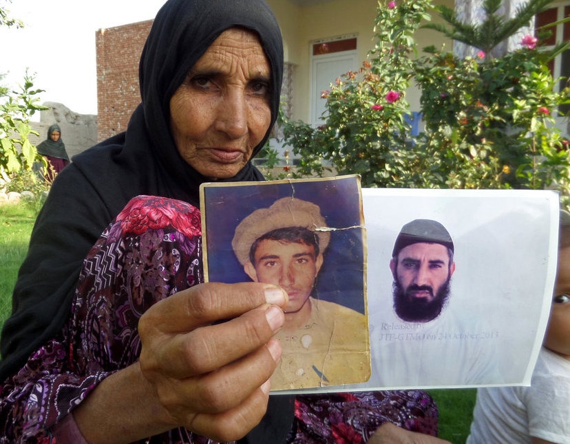Obaidullah's mother, at her home in Haiderkhil, Afghanistan, holding photos of her son on August 16, just after his release from Guantanamo (Photo: AP/Nishanuddin Khan).