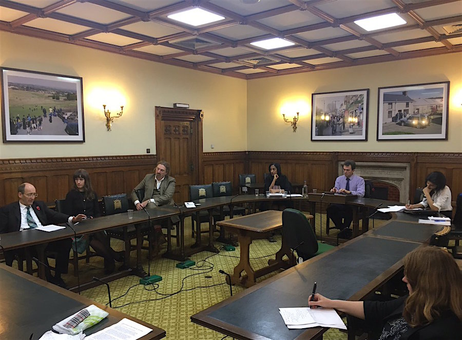 The Parliamentary meeting on Guantanamo on November 1, 2016, with Andrew Tyrie MP on the left, Chris Law MP in front of the door, Alka Pradhan to his left, and Tom Brake MP beneath the two photos on the wall (photo via Gitmo Watch).
