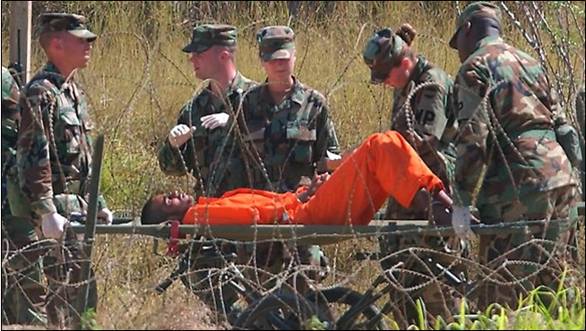 A prisoner, in the early days of Guantanamo, being moved on a gurney, as prisoners were in the prison's early years.