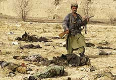 A Northern Alliance soldier poses by corpses after the Qala-i-Janghi massacre, December 2001