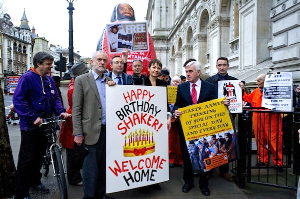 A birthday card is delivered to 10 Downing Street for Shaker Aamer's birthday on December 21, 2014, by MPs and other supporters. From L to R: Andy Worthington, the co-director of We Stand With Shaker, Jeremy Corbyn MP, Andy Slaughter MP, Peter Tatchell, Caroline Lucas MP, John McDonnell MP and John Leech MP (Photo: Stefano Massimo). The birthday card is by Dot Young, and the message, of course, was ironic, and meant to shame both the British and American governments.