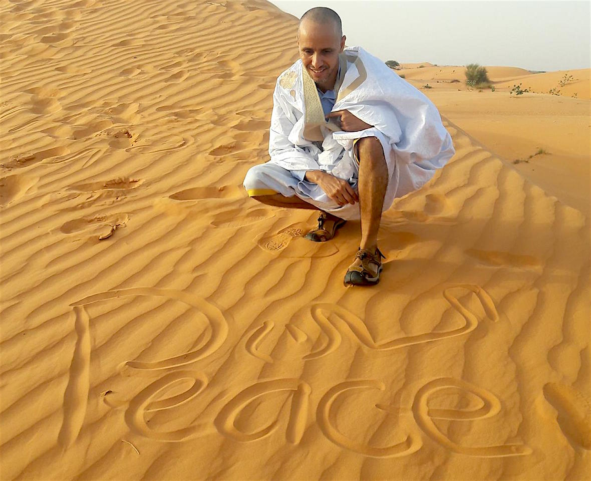 Mohamedou Ould Slahi, photographed in the desert after his release, with a message of peace. Photo from Mohamedou's Facebook page.