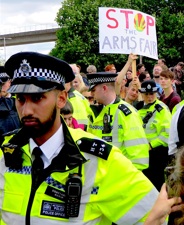 Stop the arms fair: a placard emerges from a sea of police at the Festival of Resistance against the DSEI arms fair in London's Docklands on September 9, 2017 (Photo: Andy Worthington).