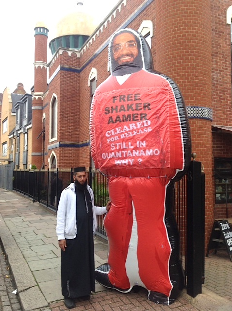 Imam Suliman Gani standing with the giant inflatable figure of Shaker Aamer that is at the heart of the We Stand With Shaker campaign, launched in November 2014.
