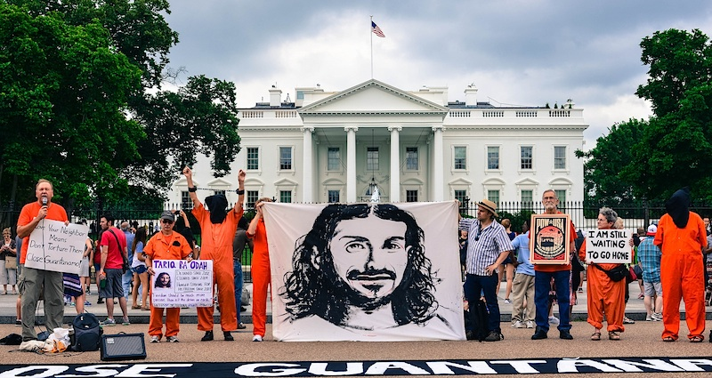Members of the campaigning group Witness Against Torture hold up a banner featuring an image of Tariq Ba Odah outside the White House in June 2015 (Photo: Matt Daloisio via Flickr).