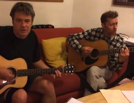 A screenshot of a video featuring Andy Worthington and Richard Clare, two of The Four Fathers, playing an acoustic version of 'Song for Shaker Aamer.'