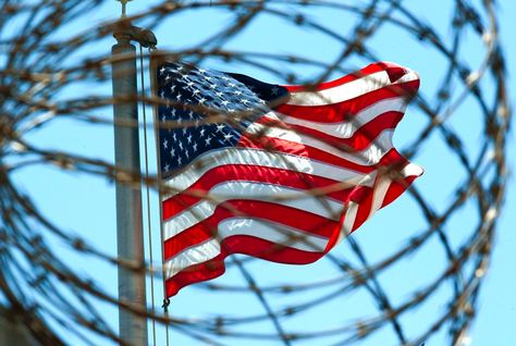 The US flag, seen through barbed wire, at Guantanamo.