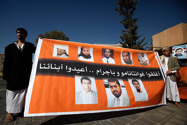 "Relatives of Yemeni prisoners in Guantanamo hold up a poster featuring their photos during a protest asking for their release in Sana'a, Yemen on January 15, 2011. The text reads: ""Close Guantanamo and Bagram, Bring back our sons"" (Photo: Khaled Abdullah/Reuters)"