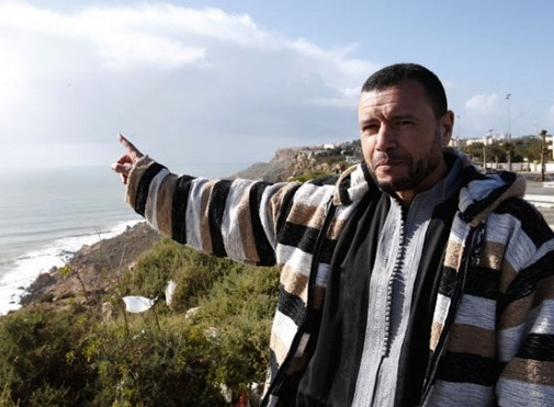 Former Guantanamo prisoner Younous Chekkouri points at the Atlantic Ocean during an interview with the Associated Press (AP Photo/Abdeljalil Bounhar).